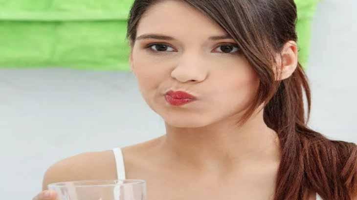 Девушка полощет рот водой