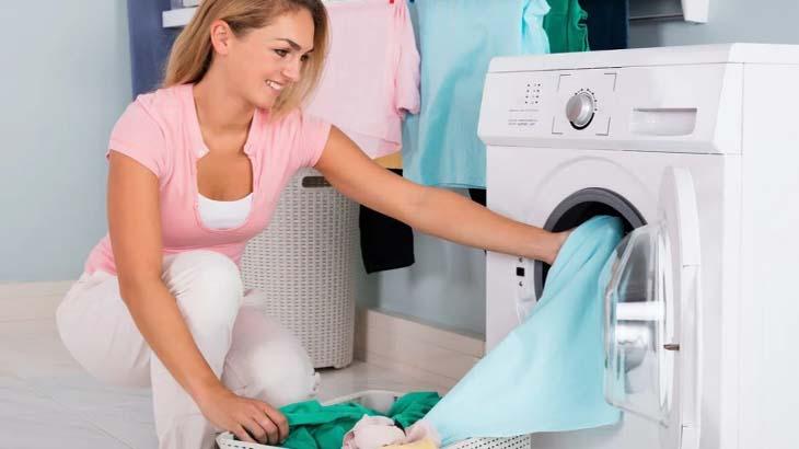 Девушка помещает белье в стиральную машину